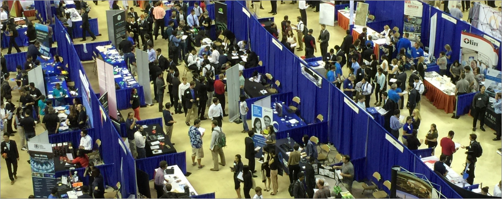 View from above of many students at multiple employer booths in a career fair.